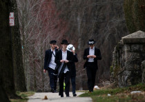 People walk on a street less than a mile away from Young Israel orthodox synagogue in New Rochelle,