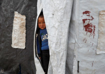 A boy looks out from inside a tent in al-Roj camp, Syria, January 10, 2020.