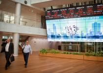 Men walking near screens showing falling stocks at the Tel Aviv Stock Exchange, in the center of Tel