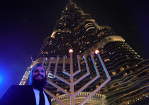 A man stands next to a giant menorah as people celebrate Hanukkah, the Jewish festival of lights, in