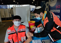 United Hatzalah volunteer vaccinating another in Jerusalem in December