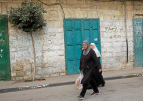 Palestinians walk past closed shops during a lockdown imposed to prevent the spread of the coronavir