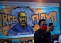 A local resident takes a selfie in front of a mural of George Floyd after the verdict in the trial o