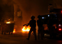 Palestinians run as Israeli military vehicle fires tear gas canisters during an anti-Israel protest