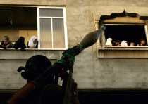 Hamas supporters watch armed Hamas militants parade in central Gaza City.