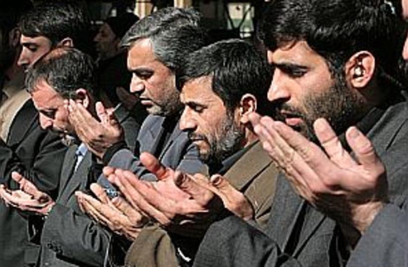 ahmadinejad prays 298 (photo credit: AP)