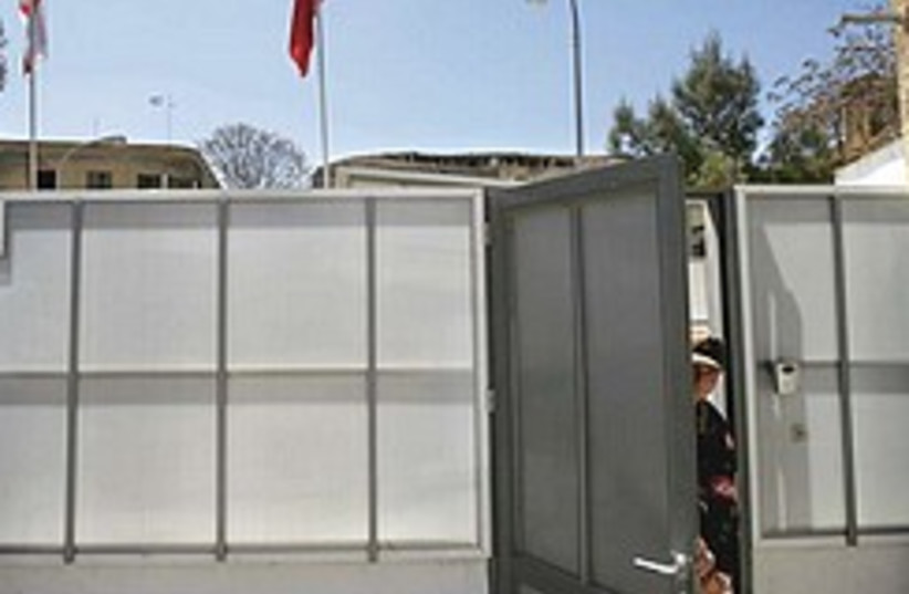Turkish soldier opens door in temporary wall by UN (photo credit: AP)