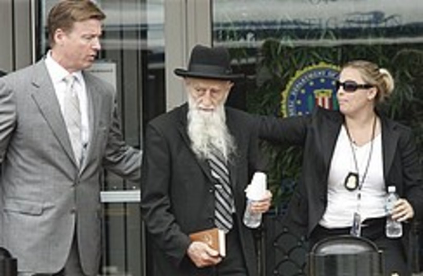 Rabbi Saul Kassin is walked to a waiting bus outsi (photo credit: AP)