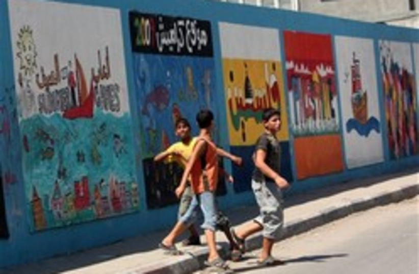 Palestinian youths walk next to a wall of a school (photo credit: AP)