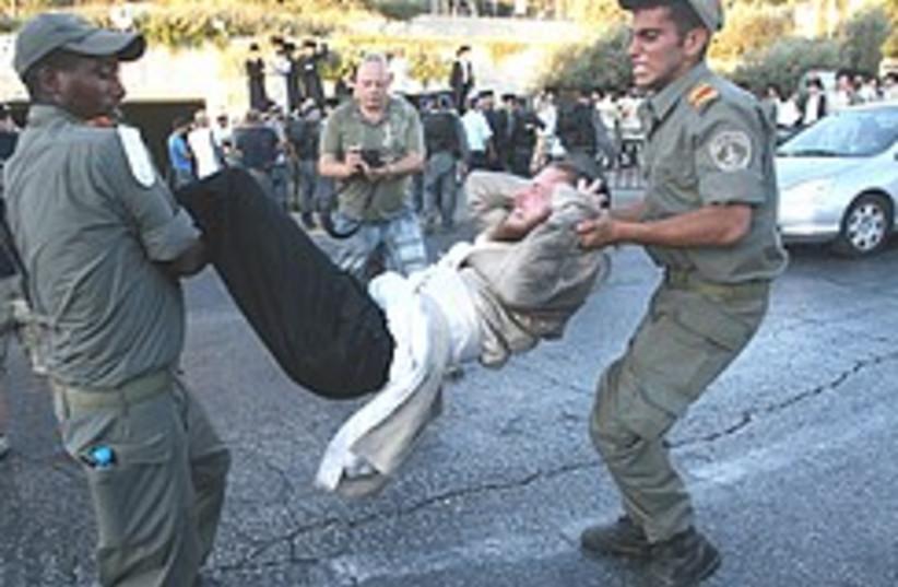 Police remove haredi protesters trying to block tr (photo credit: Ariel Jerozolimski)