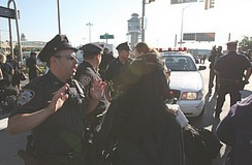 A police officer shouts instructions to a crowd ou (photo credit: AP)