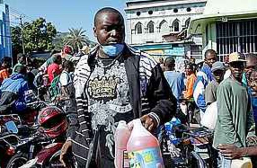 A man holds two bottle of fuel in Haiti, Thursday (photo credit: AP)