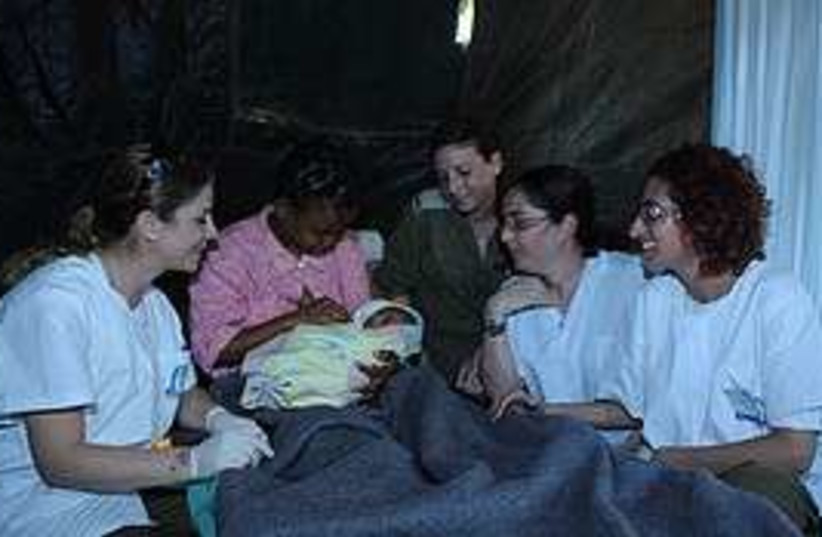 A mother holds her baby in Haiti's IDF field hospital,  (photo credit: IDF)
