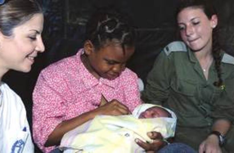 Gubilande Jean Michel holds her son (photo credit: IDF Spokesperson)