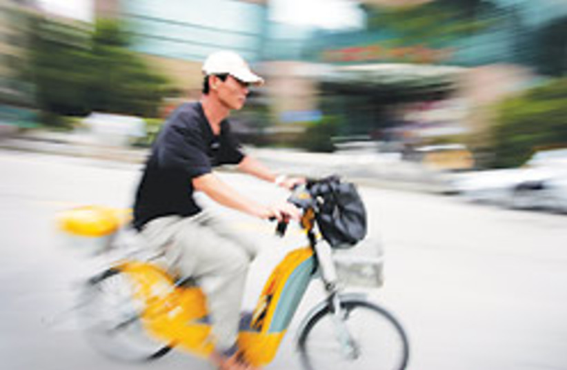 Commuters ride bicycles, mopeds and electric bicyc (photo credit: AP)