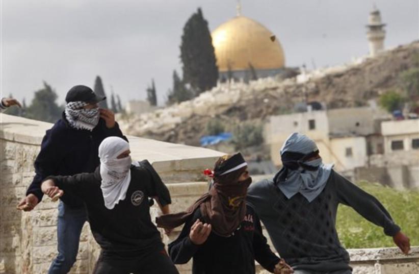 Palestinian demonstrators hurl stones (photo credit: AP)