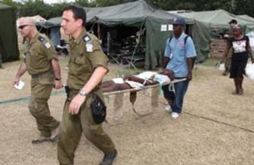 IDF doctors in Haiti w stretcher (photo credit: Associated Press)