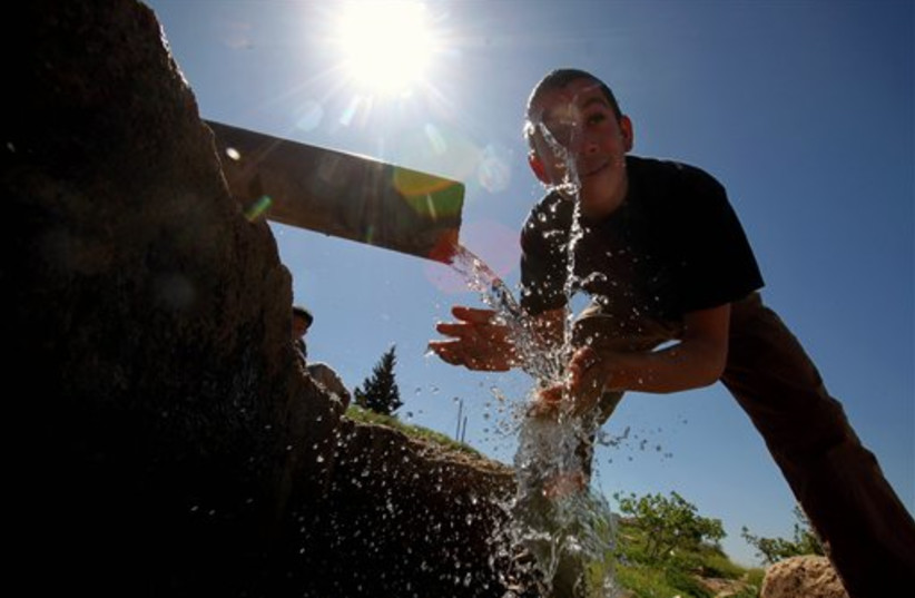 A boy washes himself in Jordan (photo credit: AP)