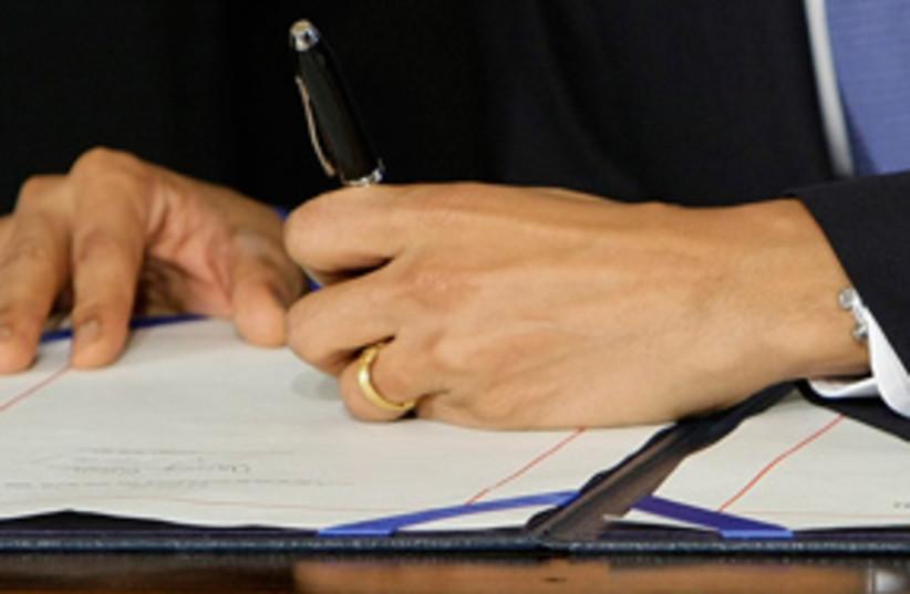 obama signs bill 311 (photo credit: AP)
