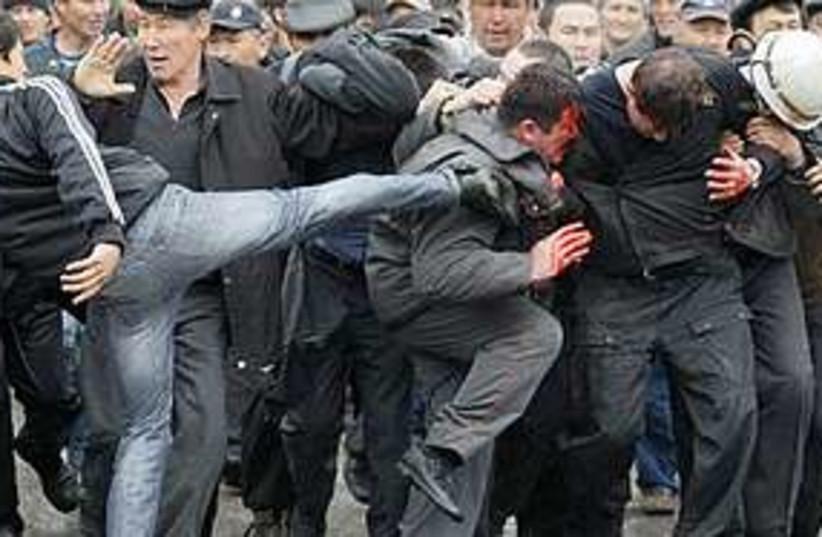 Kyrgyz protester kicks 311 (photo credit: Associated Press)
