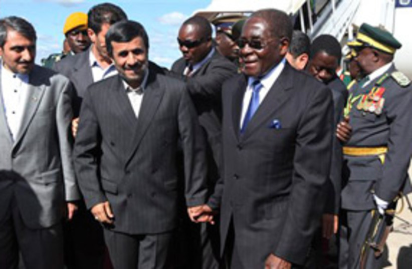 mugabe ahmadinejad hold hands311 (photo credit: AP)