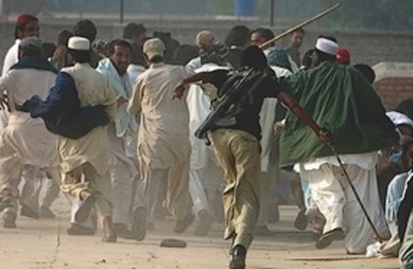 Pakistani police officer chases a mob 311 (photo credit: Associated Press)