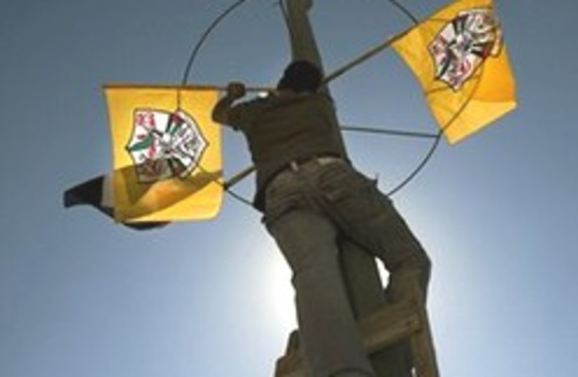 A man places Fatah flags in Bethlehem, Sunday (photo credit: AP)