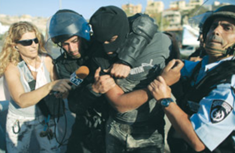 police detain masked Arab protester (photo credit: Associated Press)