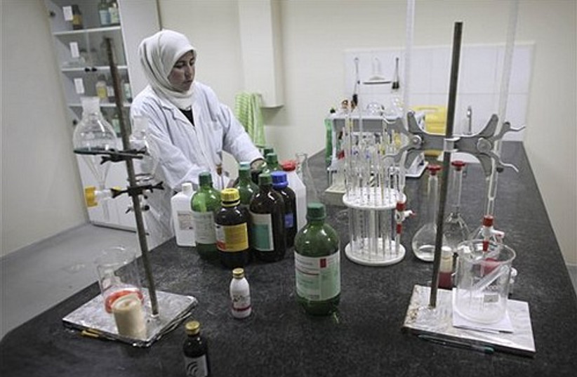A Palestinian chemist works in a quality control lab at a pharmaceutical drug manufacturing company