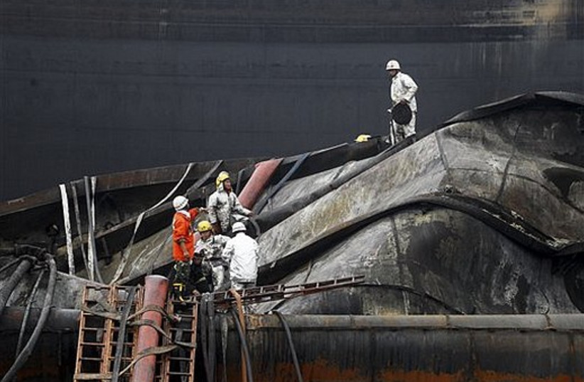 Firemen work on a burnt-out oil storage facility in Dalian, in northeast China's Liaoning province.
