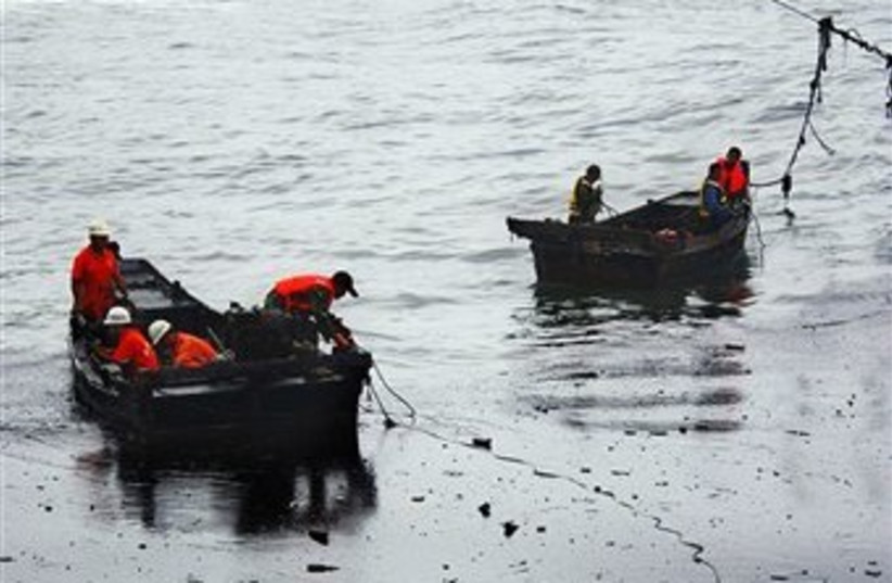 Chinese firefighters are seen on boats amongst the an oil spill near the coast of Dalian in northeas