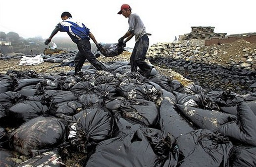 Workers move a bag on the beach polluted by crude oil after a pipeline explosion in Dalian, in north