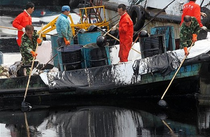 Chinese workers scoop up oil from a spill in the sea near Dalian in northeast China's Liaoning provi