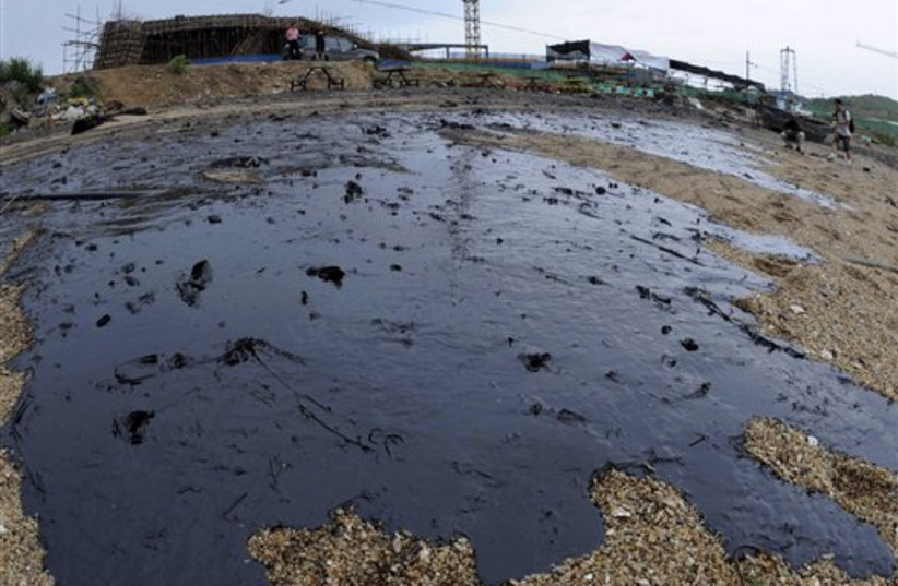 The surface of a beach covered by the spilled crude oil in Dalian, a coastal city in northeast China
