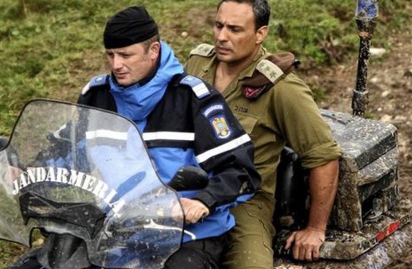 A Romanian gendarme drives an investigator wearing an Israeli uniform down a mountain path near the