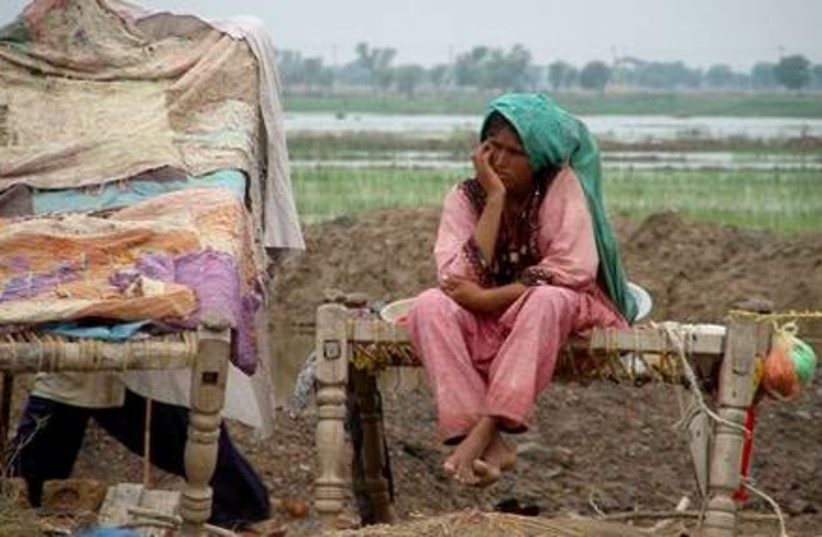 A Pakistani flood affected woman sits on the bed as she with her family members take shelter on high