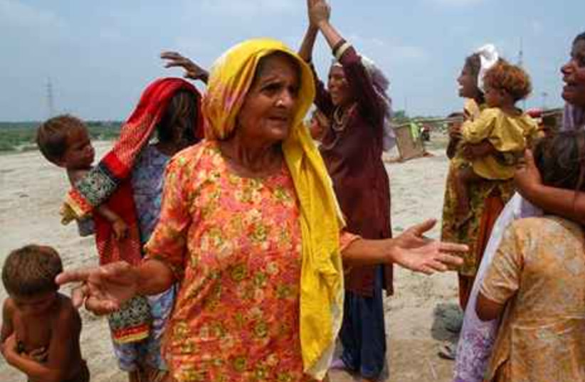 A Pakistani flood affected family react to the loss of some family members in a deeply flooded area