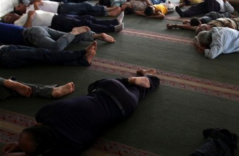 Palestinian men sleep in a mosque on the second day of the Muslim holy month of Ramadan, in the West