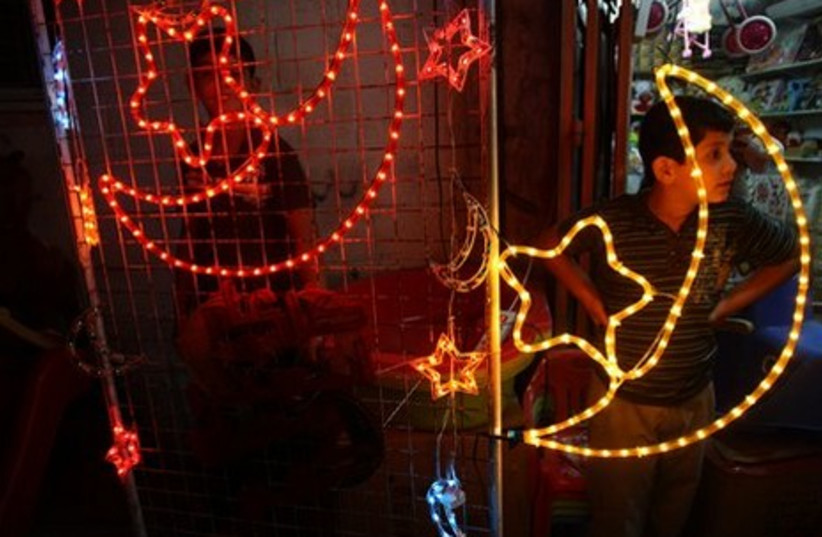 Palestinian boys stand next to a shop, decorated with Ramadan festive lights, in the West Bank city