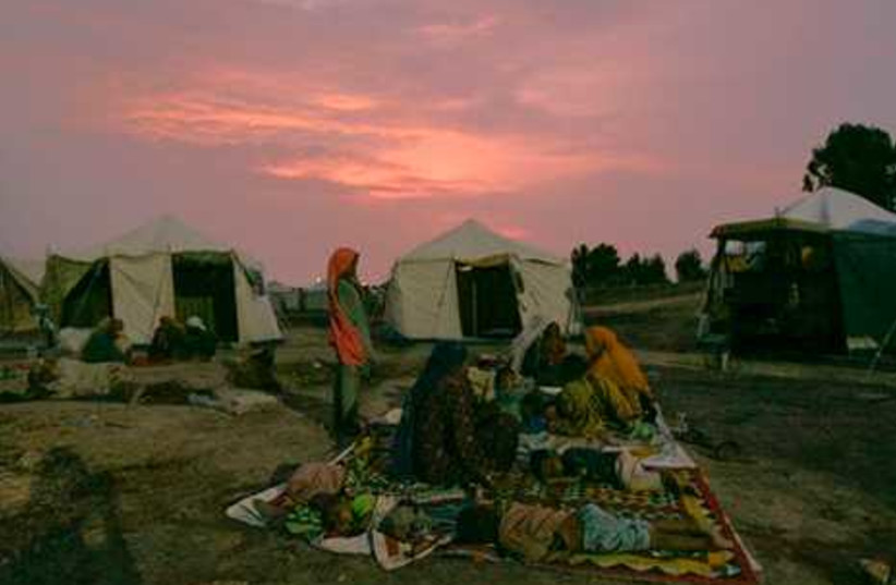 Pakistani flood affected families sit outside their tents at a camp in Sukkur, Pakistan  on Sunday,