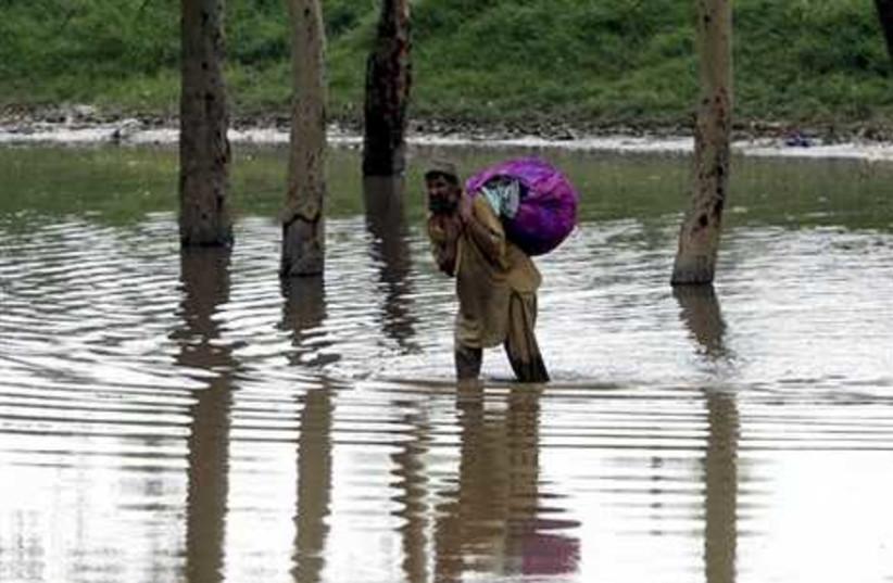 A Pakistani flood affected man carries his belongings as he wade through floodwater in Azakhel near