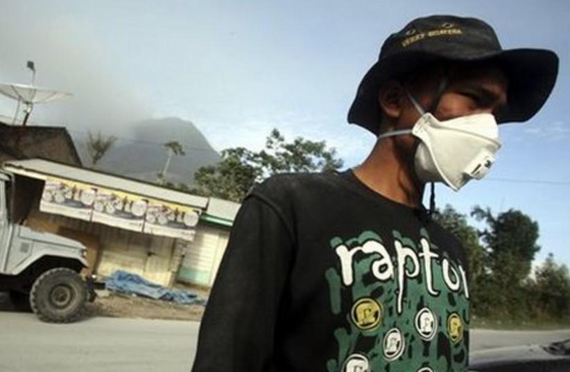 Man wears mask to avoid breathing in toxic fumes.
