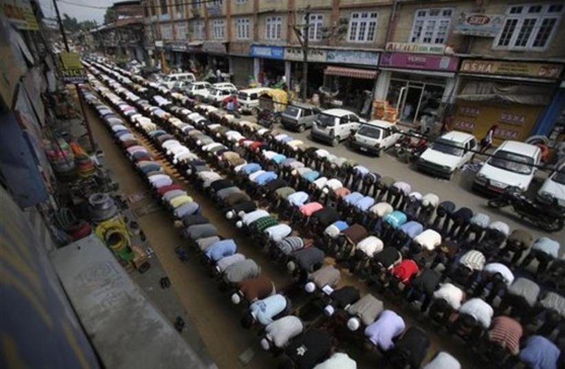 Kashmiri Muslims pray on a street on the third Friday of Ra (photo credit: AP)