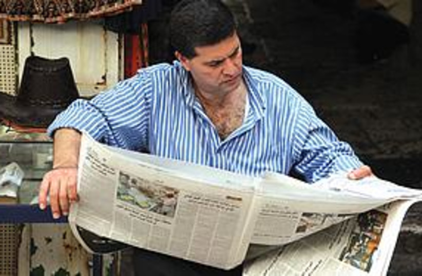 Man reads Arabic newspaper in J'lem (photo credit: Marc Israel Sellem)