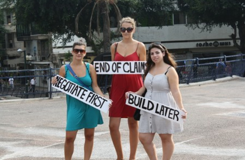 Three women holding signs advocating the freeze
