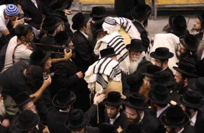 Haredim carry burnt Torah scrolls
