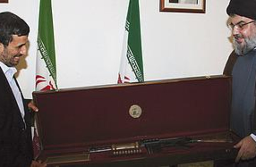 Ahmadinjead gets rifle from Nasrallah (photo credit: ASSOCIATED PRESS)