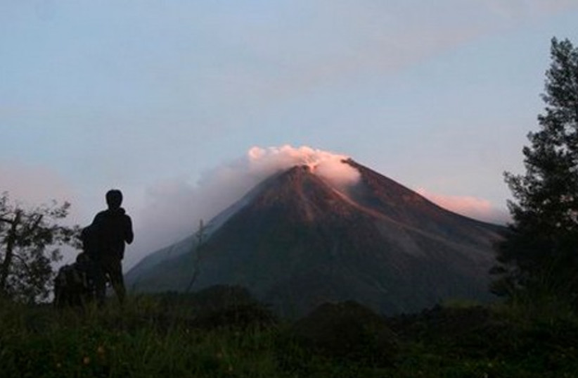 A villager watches Mount Merapi in Kaliadem, Yogya