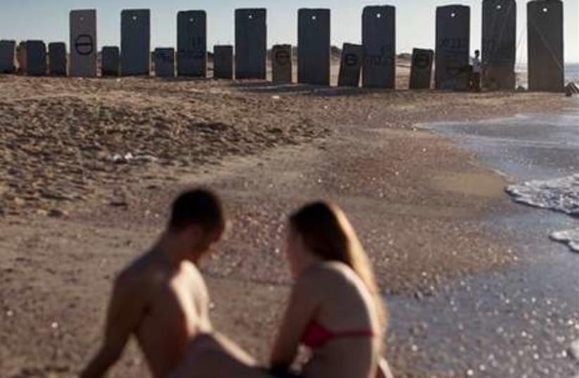 Israeli couple sit on the Zikim beach