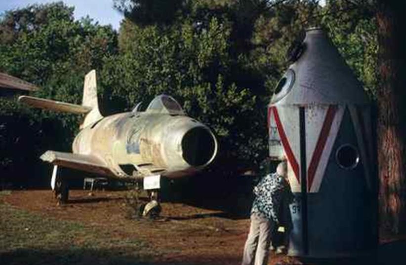Israeli woman peeps inside model of a rocket